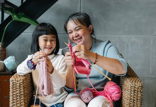 Cheerful little Asian girl with grandmother knitting with needles while sitting together on wicker armchair at home