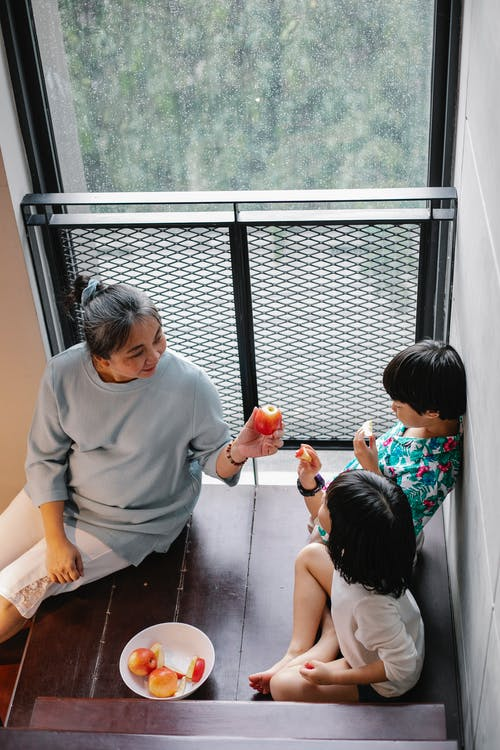 From above of positive elderly ethnic woman sitting on wooden stairs and giving fresh ripe apple to cute little grandchildren while spending time together in stylish house