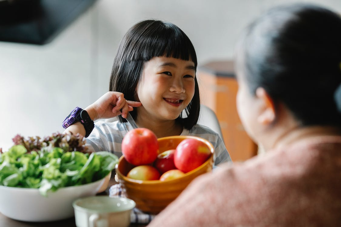Delighted cute ethnic little girl smiling while sitting at table and eating delicious fresh vegetables and fruits with unrecognizable mother