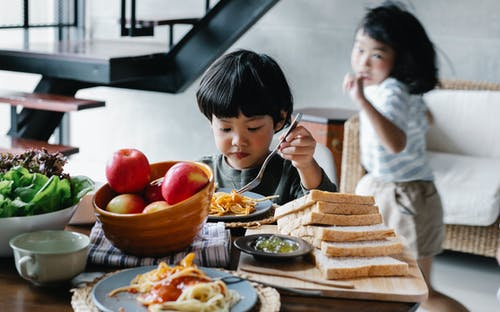 Active little Asian girl running behind brother having lunch in kitchen