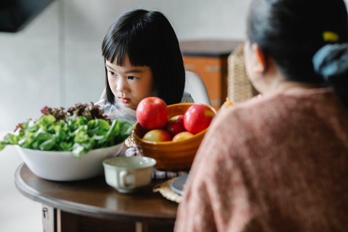 Ernstige Etnische Meisje Zittend Aan Tafel Met Moeder Tijdens De Lunch En Wegkijken