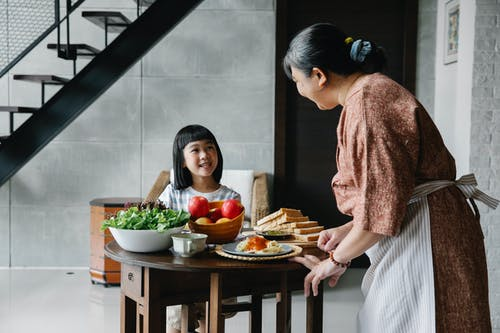 Delighted little Asian girl smiling and speaking with grandmother while having lunch at home
