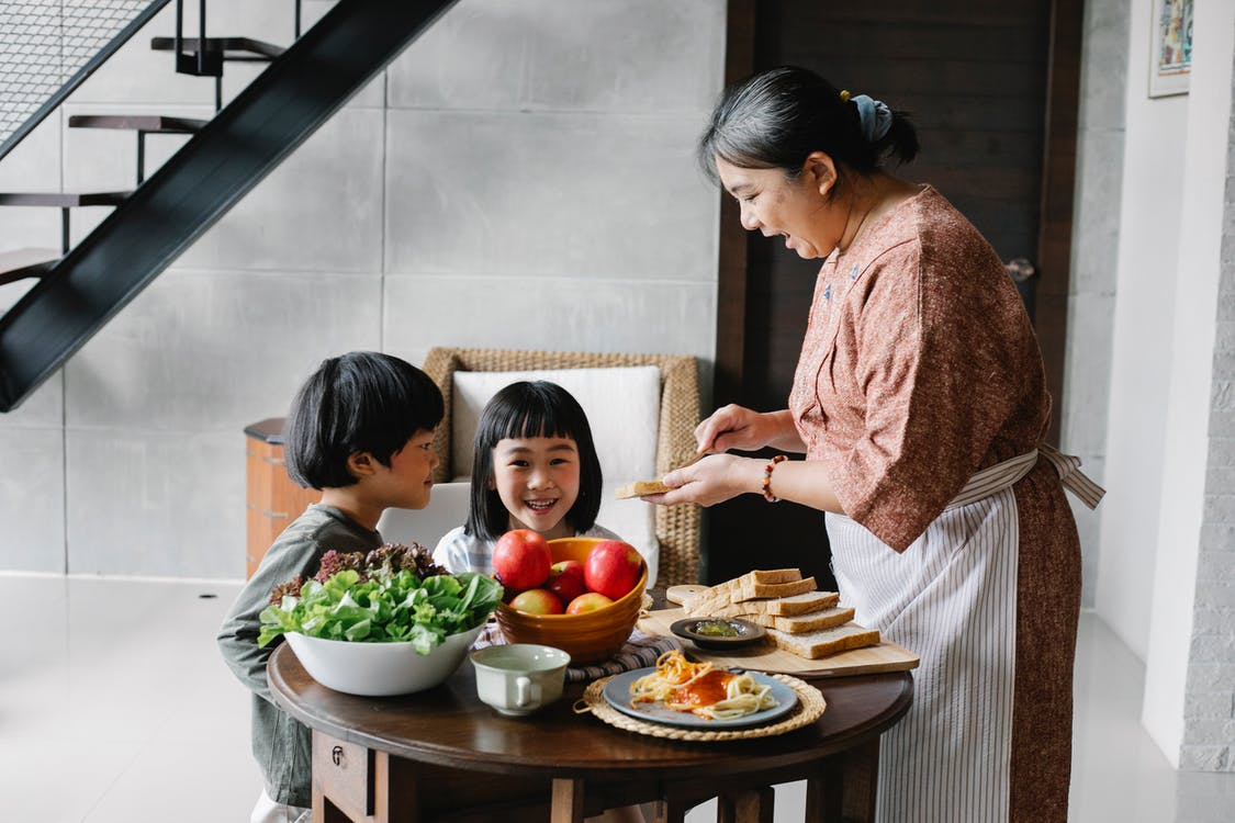 Side view of positive senior Asian female in apron spreading butter on bread while preparing breakfast for funny little grandchildren sitting at round table in cozy kitchen