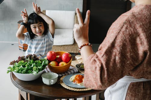 Happy little ethnic girl having fun with faceless mother showing V sign during lunch