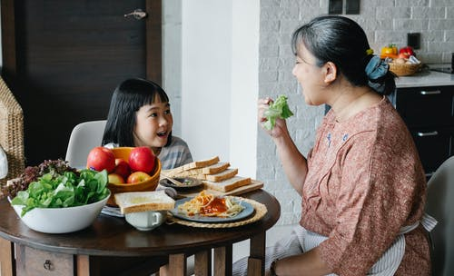 Delighted ethnic little girl looking at grandmother eating healthy salad