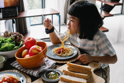 Cute Asian little girl enjoying delicious spaghetti during lunch at home
