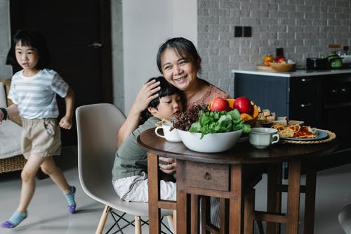 Active little Asian girl running behind grandmother and brother embracing at table during breakfast