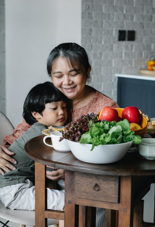 Positive senior ethnic female and cute little grandson hugging each other while having breakfast together at table with healthy salad and fruits in sunny morning