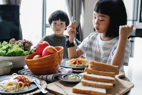 Calm little ethnic siblings eating yummy spaghetti during lunch at home