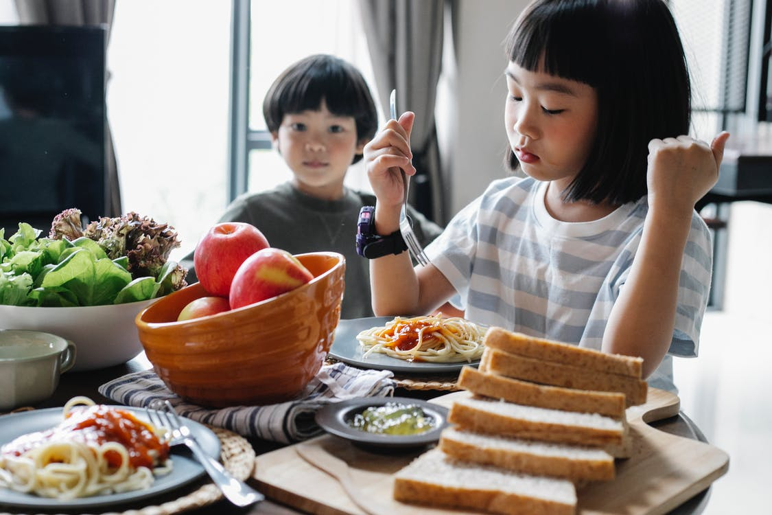 Serious little Asian girl eating delicious pasta with cute brother while sitting at table with healthy salad and apples on sunny day