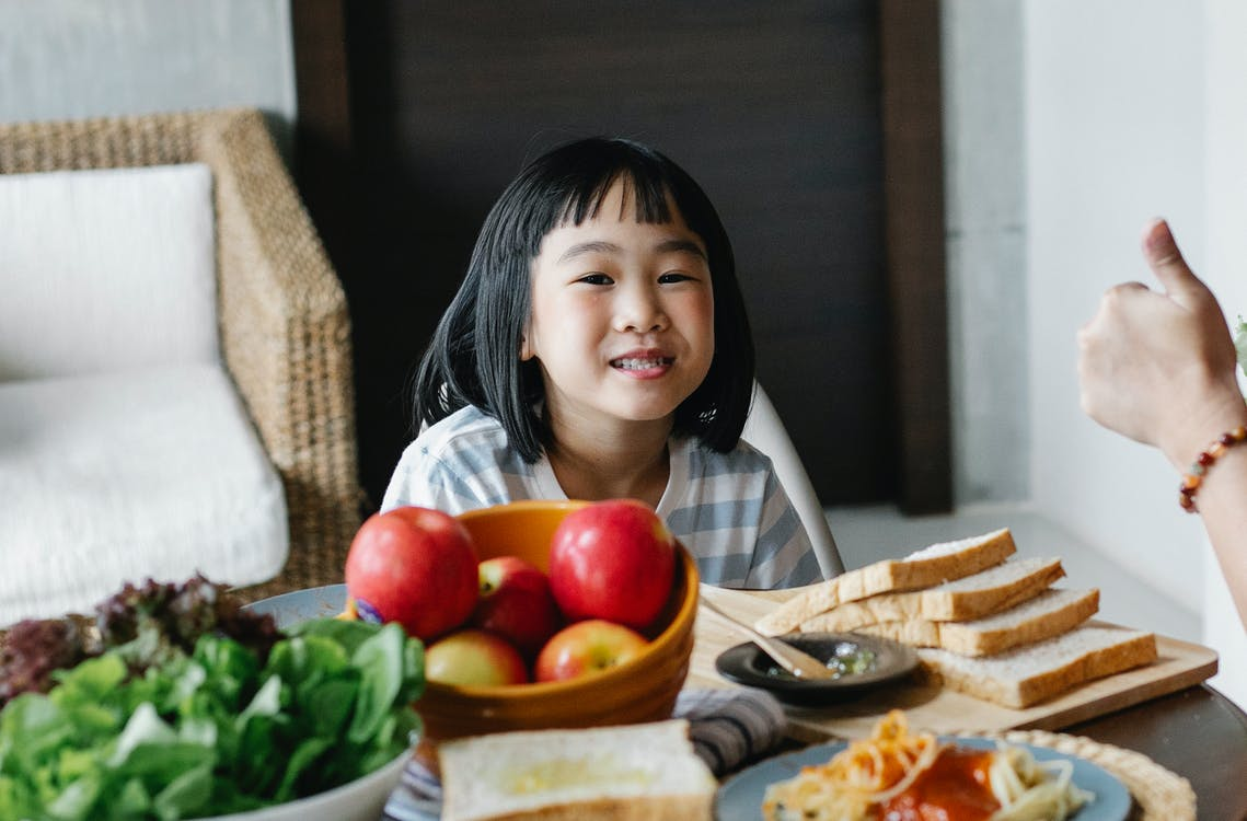 Positive cute little Asian girl sitting at table with bowl of apples and green salad served with sliced bread and spaghetti during lunch at home