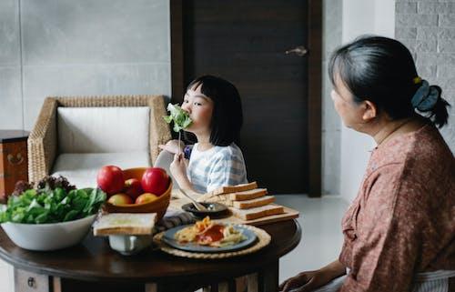 Маленькая азиатская девочка ест здоровый салат, сидя за столом с бабушкой