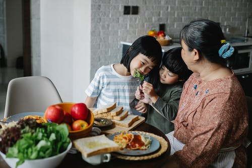 Cheerful little Asian siblings feeding each other while having lunch together with happy grandmother in modern kitchen