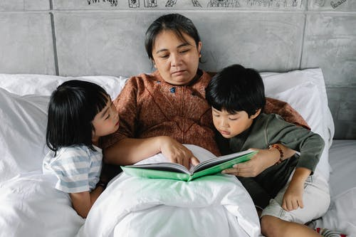 From above of focused elderly Asian woman lying in comfortable bed and reading interesting book for attentive little grandchildren