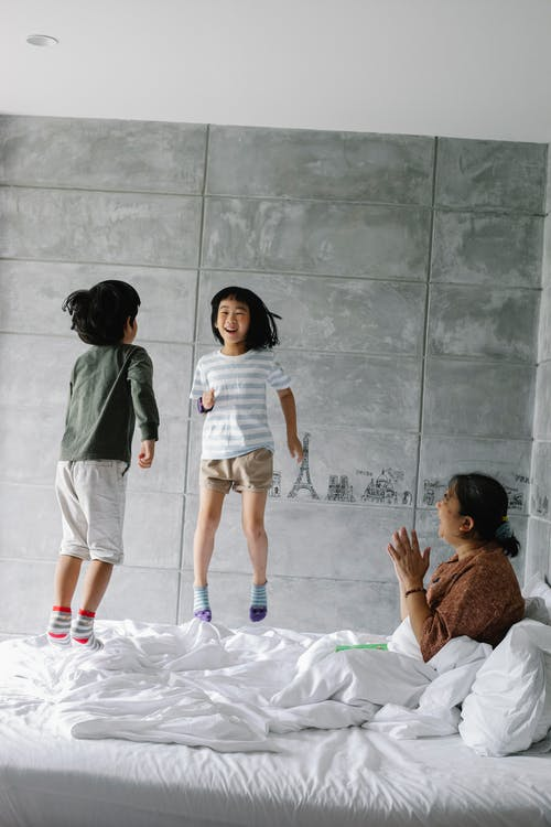 Adorable cheerful little Asian siblings jumping on bed and laughing while having fun together with happy grandmother at home
