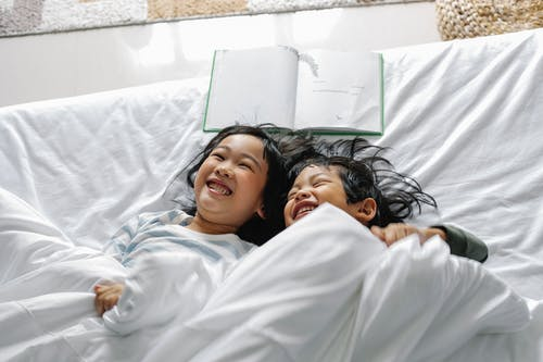 Hermanos Pequeños Asiáticos Positivos Riendo Mientras Se Relaja En La Cama