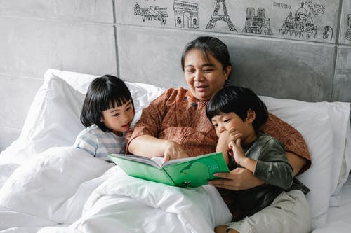 From above of adorable little Asian children lying on soft white bed with senior grandmother and reading interesting fairytale attentively