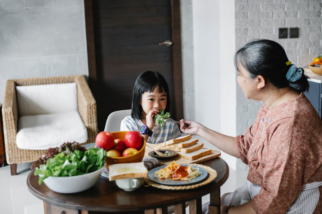 Ethnic daughter eating lettuce leaf while having healthy meal with mother in modern apartment