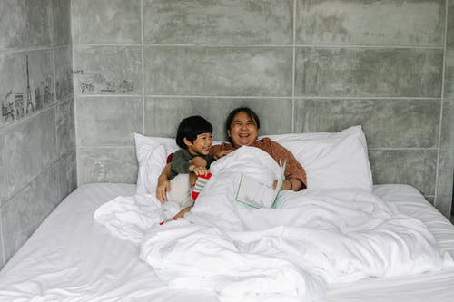 Happy ethnic mother laughing with son in bed