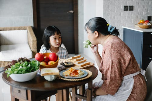 Ethnic mom giving salad leaf to girl while eating together at table in lunch time
