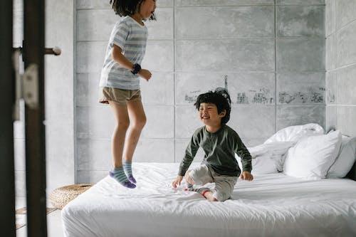 Happy ethnic kids having fun on bed
