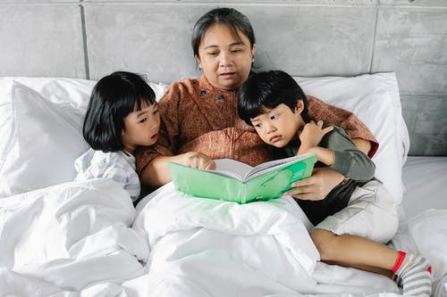 From above of Asian grandmother lying with little daughter and son during bed time and reading book