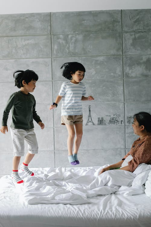 Ethnic siblings jumping on bed in bedroom