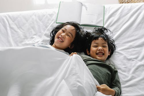 From above of Asian siblings laughing happily while lying in bed under soft blanket