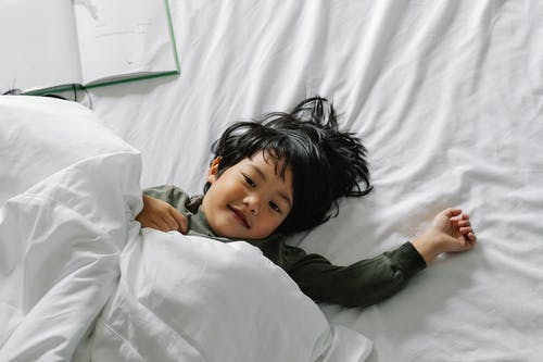 Ethnic boy lying in bed after sleep