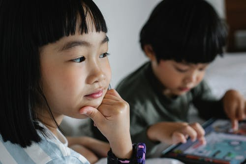 Crop concentrated ethnic girl touching chin while sitting near sibling playing game in modern device