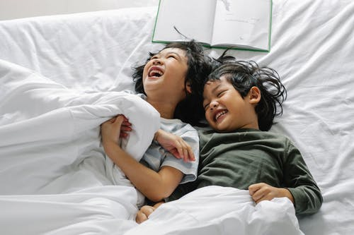 Ethnic kids laughing while lying in bed