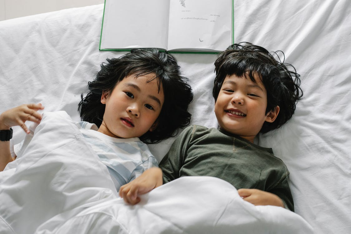From above of happy Asian boy and girl lying on bed with book under blanket and looking at camera in bedroom