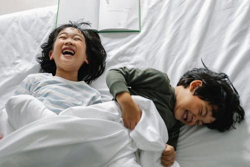 Smiling Asian kids in bed