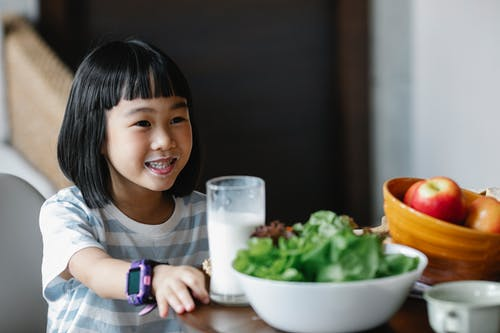 Happy Asian girl drinking milk