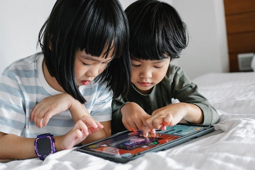 Attentive Asian boy and girl playing video game on modern tablet while lying on bed in bedroom in morning time