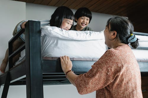 Grandmother near bunk bed with Asian kids