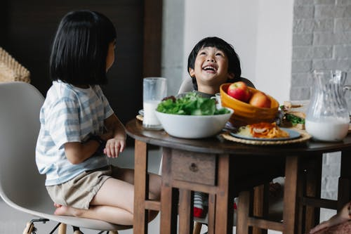 Cheerful Asian children having breakfast