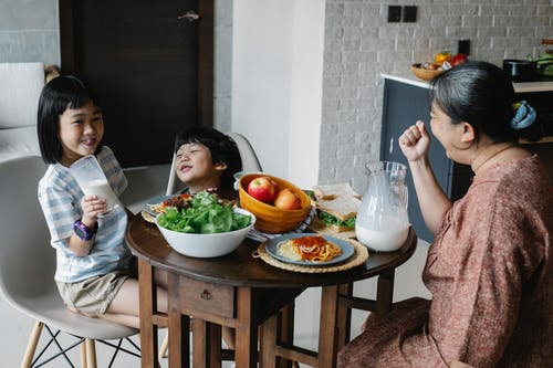 Cheerful Asian boy and girl sitting at served table with grandmother while having breakfast and drinking milk in morning on kitchen