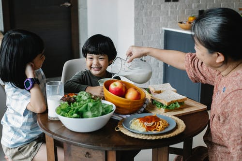 Grandmother pouring milk from jug in plate while sitting at served table with Asian boy and girl during breakfast in kitchen