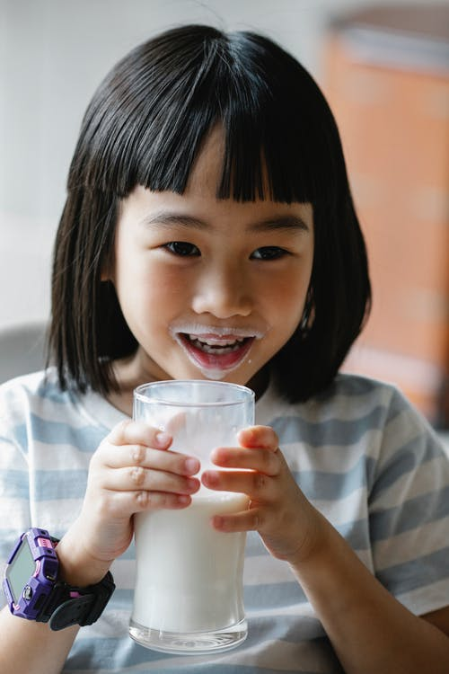 Positive Asian preteen with milk on lips and glass of healthy beverage in hands looking away while sitting in kitchen