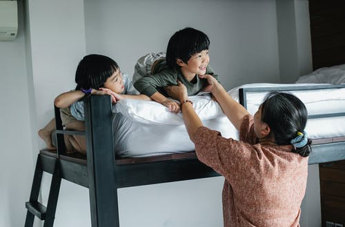 Asian kids on bunk bed near grandmother