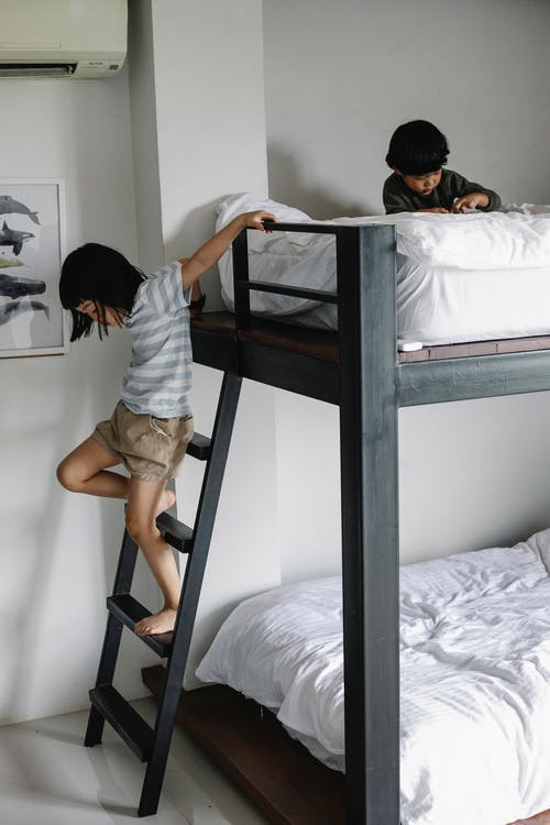 Asian girl getting down stair of bunk bed in bedroom with boy sitting on bed in morning in light apartment