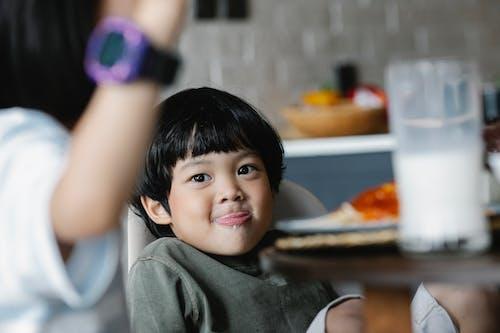 Положительный азиатский мальчик лижет губу