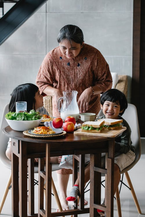Grandmother standing near Asian boy and girl sitting at table served with sandwiches and fruits with milk during breakfast in kitchen