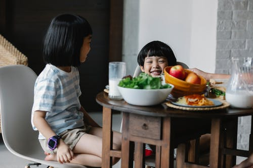 Cheerful Asian boy and girl sitting at served table with bowl of fruits and jug of milk in kitchen in breakfast time