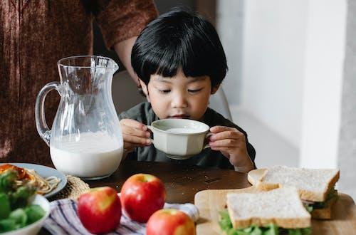 Азиатский мальчик пьет молоко на кухне