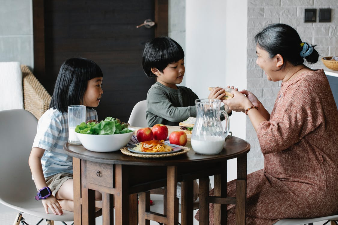 Asian boy and girl sitting at served table with fruits and milk with grandmother during breakfast time in morning on kitchen