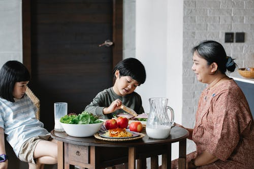 Asian grandmother feeding children in kitchen