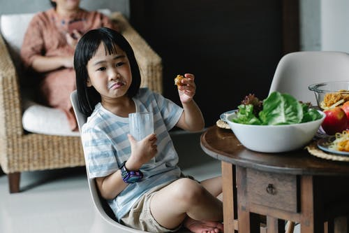 Asian preteen with grimace sitting with glass of milk near wooden table with served food in kitchen during breakfast with blurred background