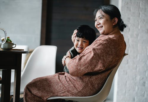 Asian grandmother hugging little boy